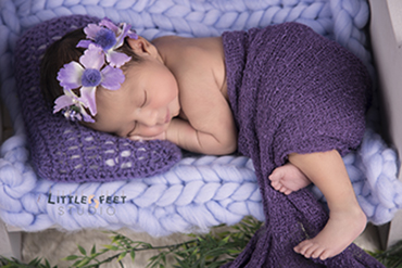 The photographer clicks the newborn baby picture while he was sleeping at littlefeetstudio.